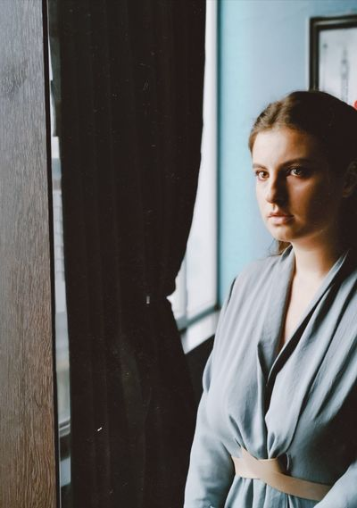 Portrait of beautiful young woman standing against window at home