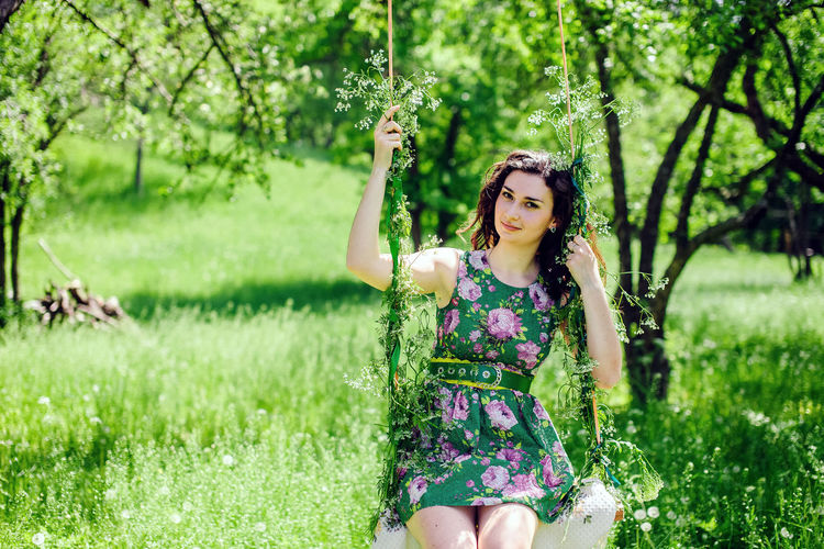 woman ride on swing. Summer time leisure and relaxation. One Person Young Adult Grass Beauty Beautiful Woman Hairstyle Plant Long Hair Green Color Hair Nature Leisure Activity Outdoors Adult Summer Green Color Green Summertime Brunette Woman Countryside Village Springtime Swing