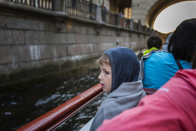 Boy looking away while standing by canal