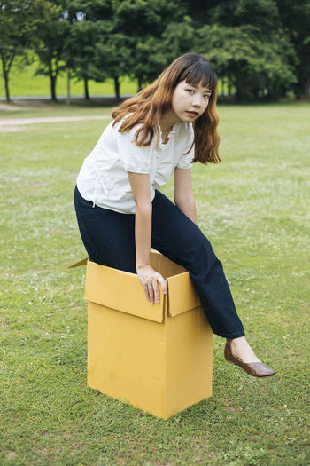 Portrait of young woman standing in cardboard box