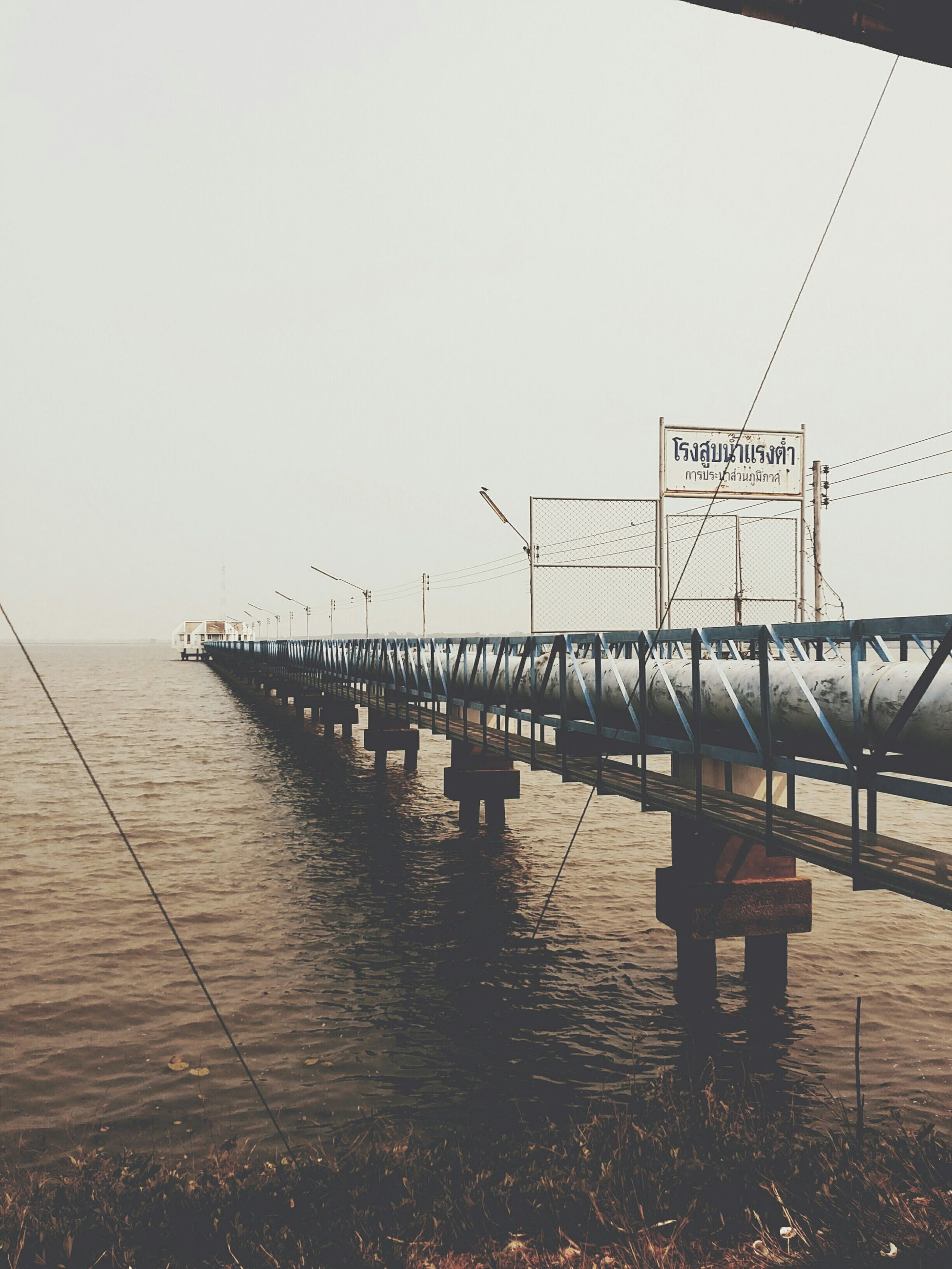 water, sea, clear sky, pier, horizon over water, copy space, tranquility, tranquil scene, nature, sky, transportation, bird, beach, outdoors, scenics, incidental people, sunset, wood - material, built structure, beauty in nature