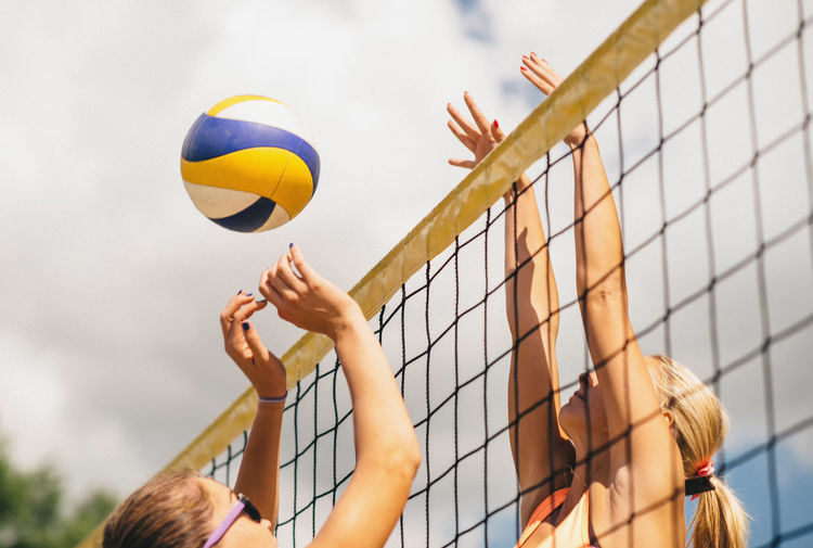 Beach Volleyball Duel on the Net 20s Beach Volleyball Caucasian Girls Cloudy Sky Daytime Horizontal Composition Sunny Activity Ball Bikini Blonde Hair Competition Girls Jumping Match Net - Sports Equipment Outdoors Playing Sand Sport Team Sport Tournament Volleyball Women Only Young Woman