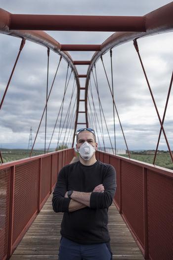 Portrait of man wearing mask standing on footbridge against sky