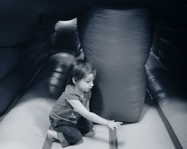 Side view of girl plying in bouncy castle