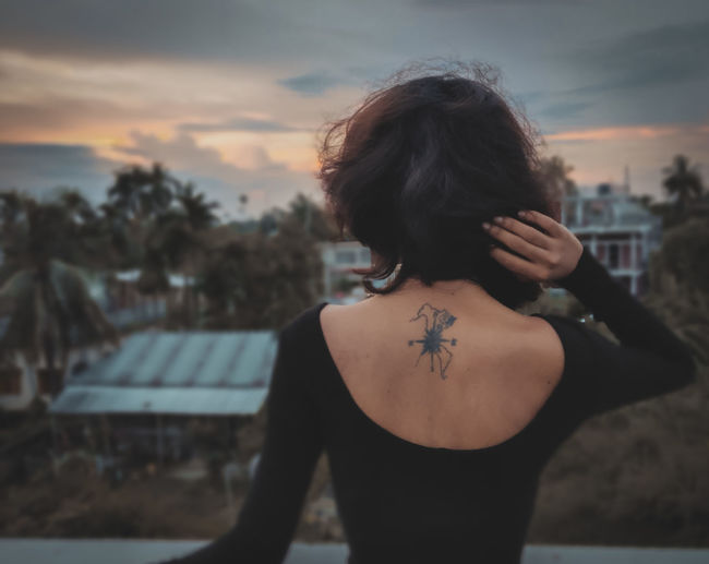 Rear view of woman looking at city during sunset