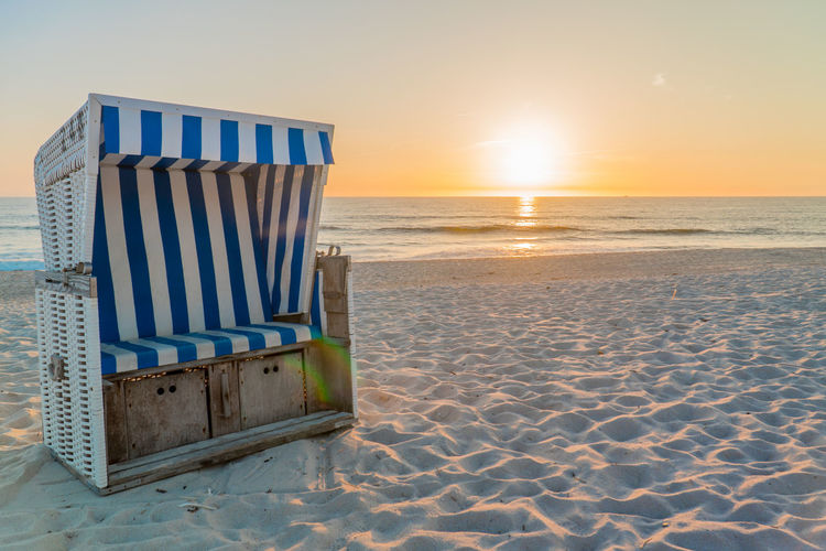Beach Land Sand Sea Sky Sunset Water Tranquil Scene Tranquility Horizon Horizon Over Water Nature Beauty In Nature Scenics - Nature Absence Hooded Beach Chair Idyllic Striped No People Sun Outdoors
