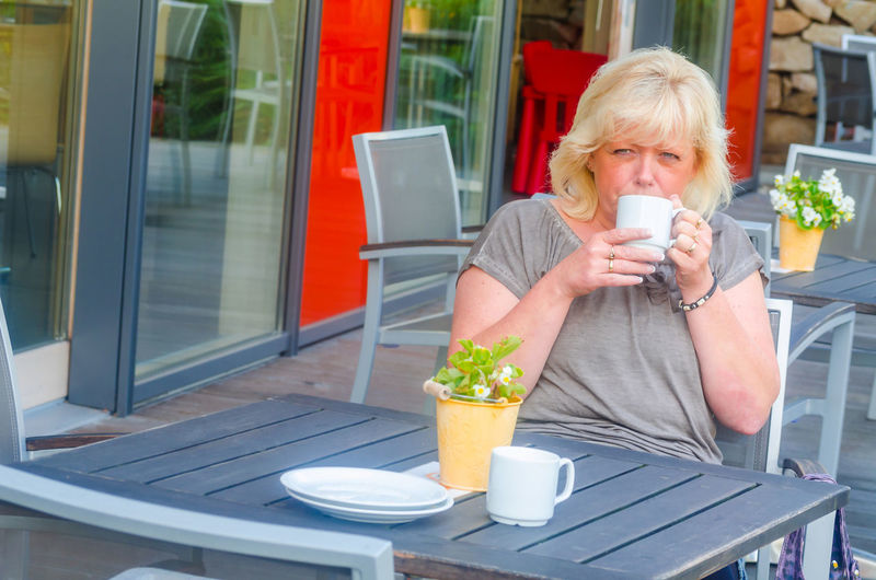 Portrait of woman drinking coffee while sitting at sidewalk cafe