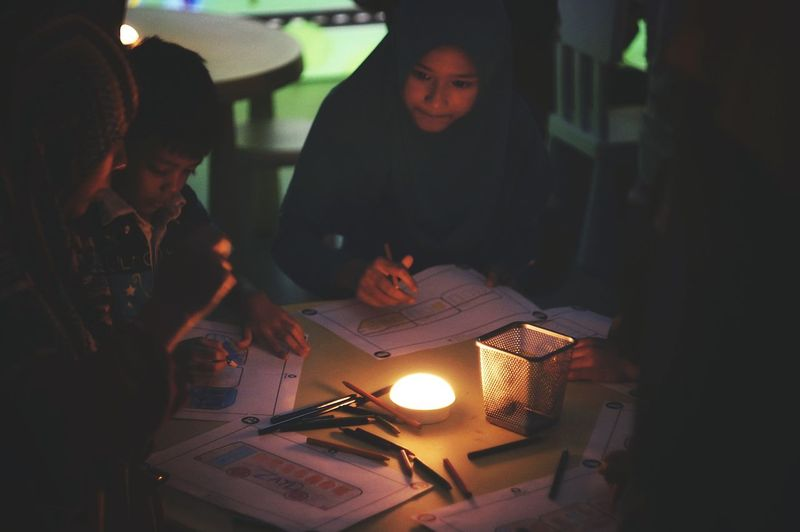 People working on table in illuminated room