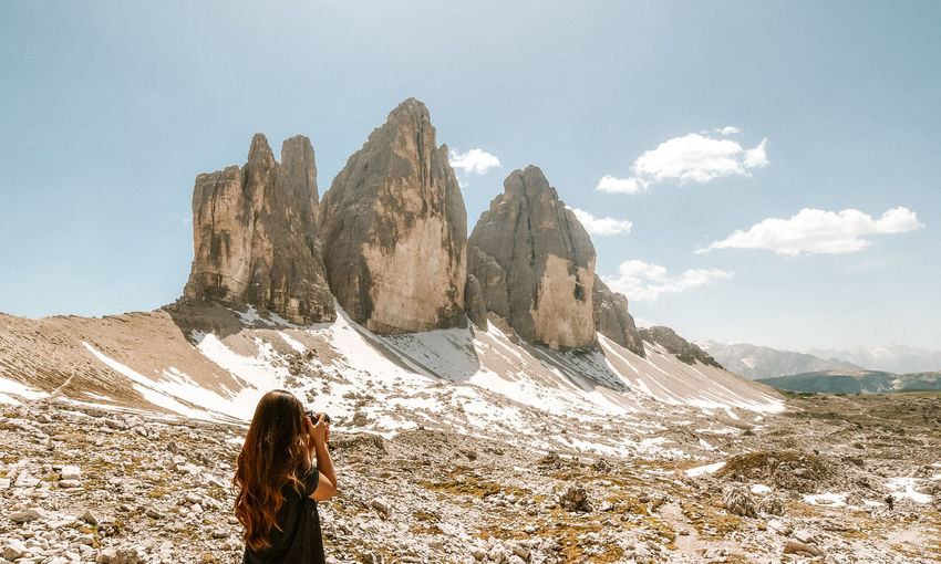 Rear view of woman with mountain range against sky