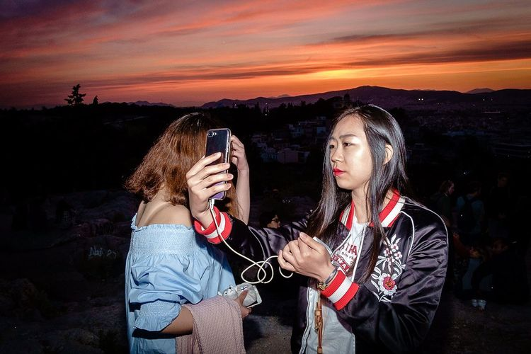 Sunset selfie X-Pro1 Fujifilm X-Pro1 Street Hunters Streethunters Street Photography Streetphotography Wireless Technology Smart Phone Portable Information Device Photography Themes Mobile Phone Communication Selfie Self Portrait Photography Photographing Sunset Sky Holding