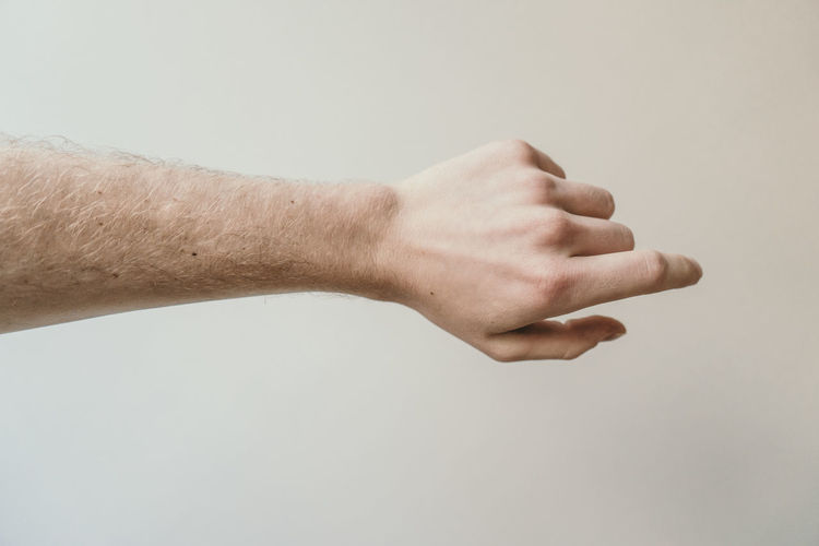 Cropped hand of man against beige background
