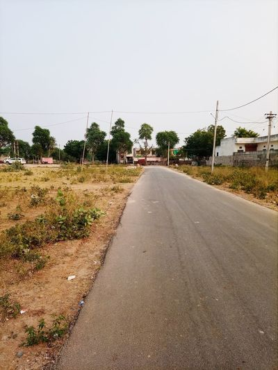 Empty road by plants in city against clear sky