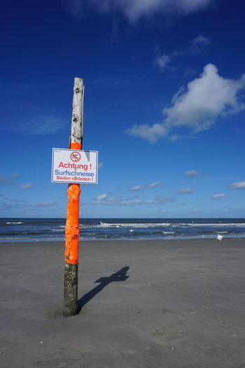Information sign on wooden post at beach against sky