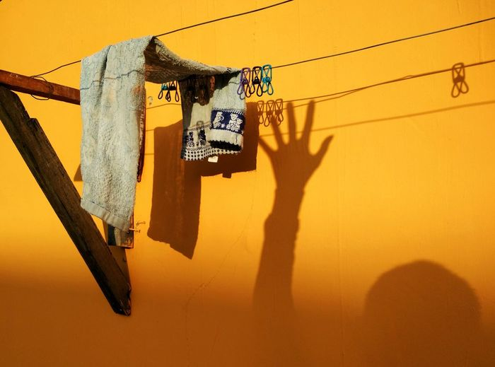 Low Angle View Of Clothes Line Against Yellow Wall