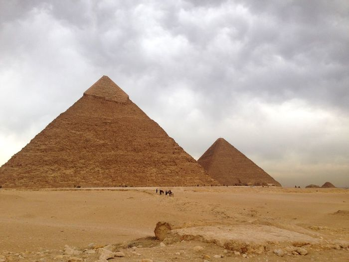 Pyramid in desert against cloudy sky