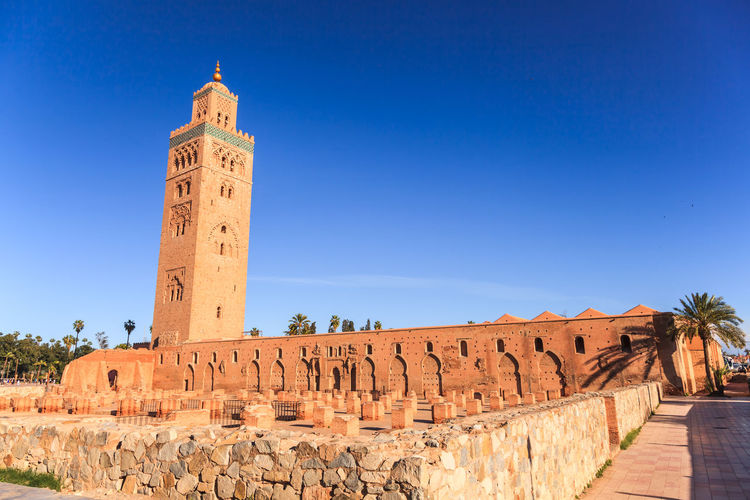 Koutoubia Mosque in Marrakech, Morocco Moroccan Architecture Palm Tree Architecture Blue Blue Sky Building Exterior Built Structure Clear Sky Day Famous Places History Islamic Architecture Low Angle View Minaretsofworld Mosque No People Outdoors Religion Sky Temple - Building Tower Travel Destinations