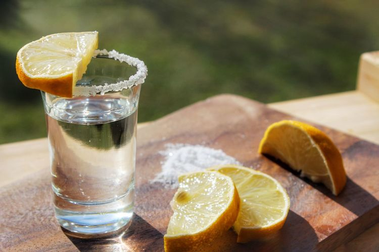Close-up of tequila shot with lemons slices on cutting board