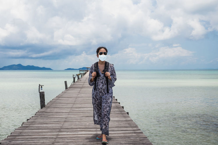 Woman in protective  mask standing on pier over sea against sky