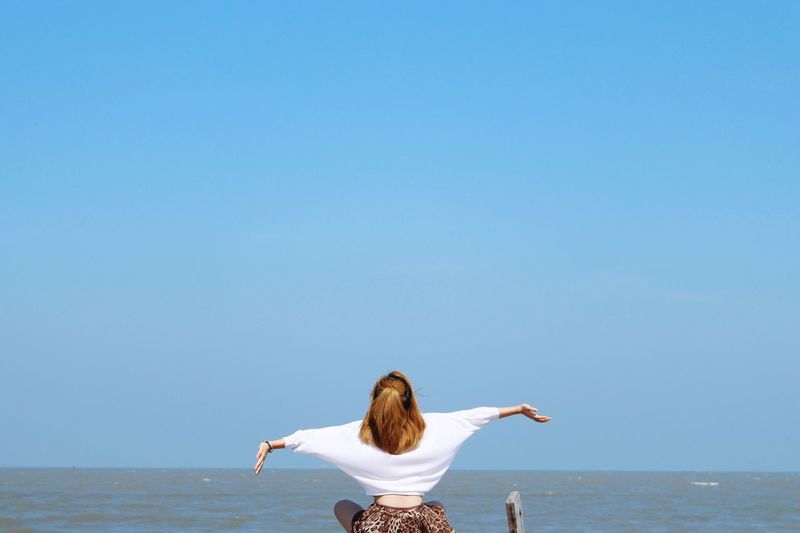 Rear view of woman in sea against clear sky