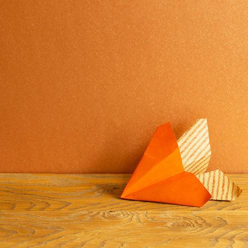 Umbrella on paper against orange wall