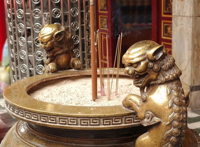 Incenses in cauldron amidst statues outside temple