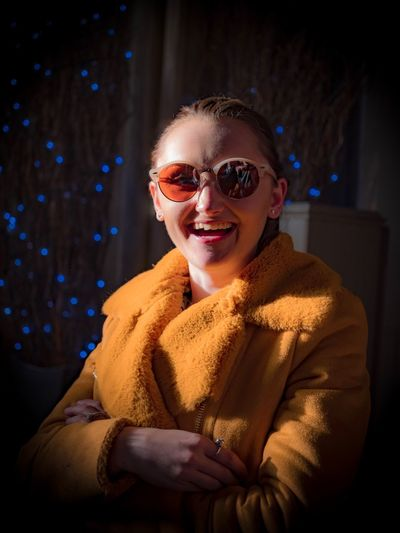 Portrait of cheerful young woman wearing sunglasses and coat at home