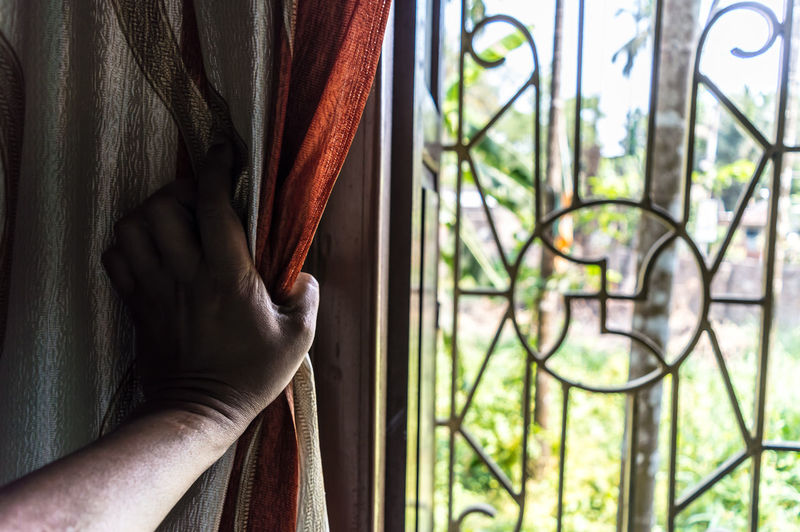 Close-up of person hand on window