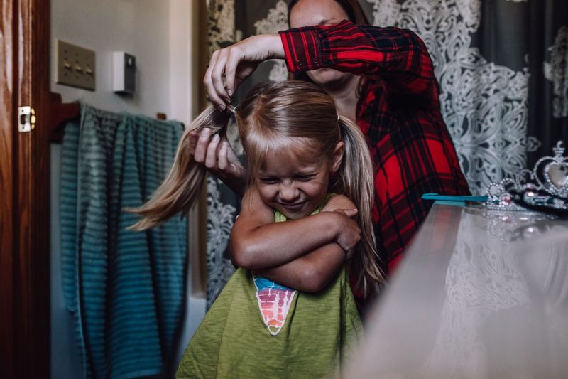 Mother combing hair of daughter at home