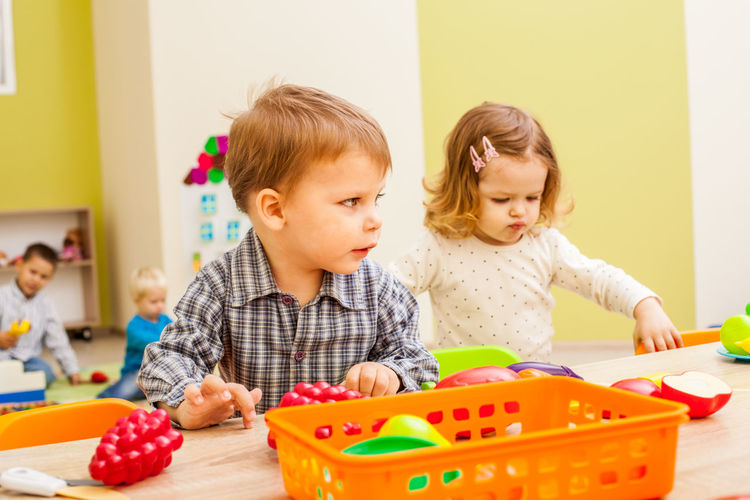 Boy and girl playing with toy at kindergarten