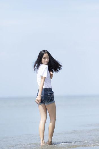 Full length portrait of girl at beach against sky