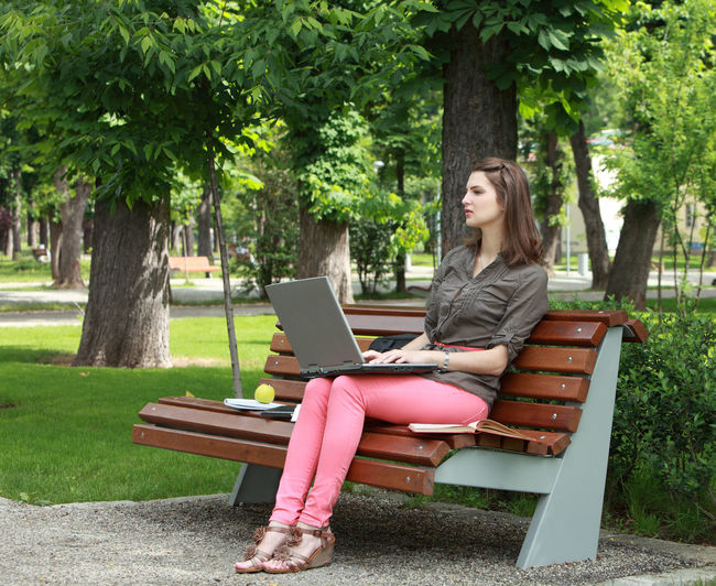 Young woman with a laptop sitting on a bench in an urban park. Sitting One Person Young Adult Wireless Technology Laptop Using Laptop Bench Computer Technology Casual Clothing Park Adult Beautiful Woman Outdoors Park Bench Woman Young Woman Learning Student Resting Nature