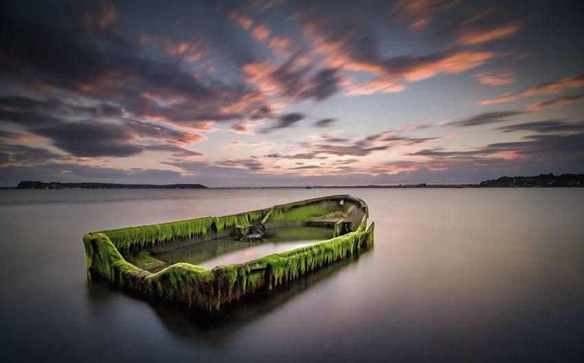 Moss Grown Boat On River Against Sky