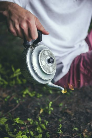 Cropped Image Of Person Holding Teapot On Field
