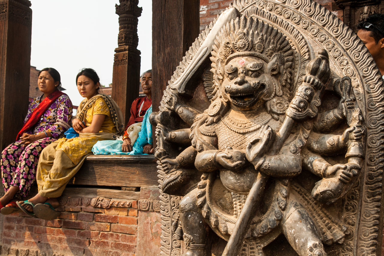 religion, spirituality, architecture, place of worship, travel destinations, statue, building exterior, history, travel, outdoors, ancient, low angle view, built structure, day, sitting, sculpture, women, adult, mammal, young adult, ancient civilization, people, sky, adults only