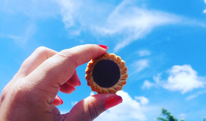 Cropped hand of woman holding biscuit against blue sky
