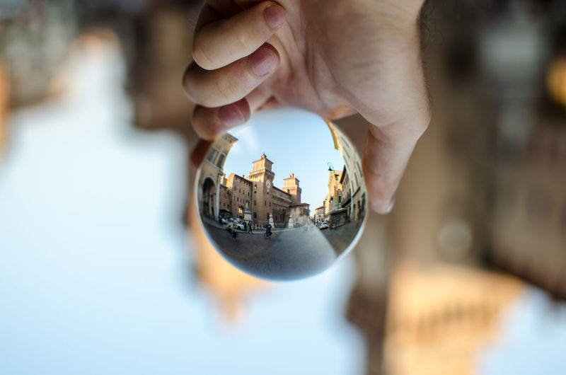Cropped hand holding crystal ball with street and buildings reflection in city