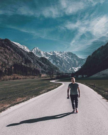Full length of man skateboarding on road against mountains