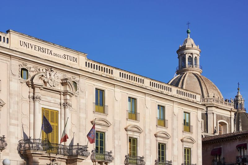 University of Catania, Sicily University Façade Sicily Clear Sky Catania Italy Dome Cupola Blue Sky Historic Historical Building Architecture Built Structure Building Exterior Low Angle View Day No People City Urban Landmark Flags Balcony Windows