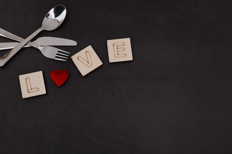 Indoors  Still Life Table No People Text Directly Above Kitchen Utensil Paper Spoon Communication High Angle View Love Eating Utensil Positive Emotion Food And Drink Heart Shape Copy Space Western Script Food Black Background Message Blank Valentine's Day  Valentine's Day - Holiday