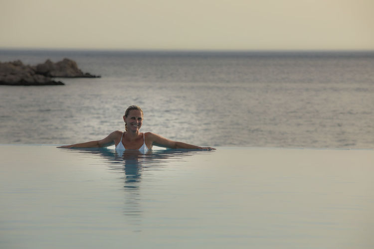 Portrait of smiling woman in infinity pool by sea during sunset