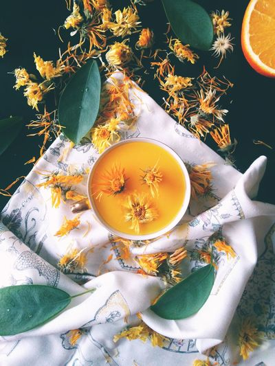 High angle view of cup of juice and flowers on table