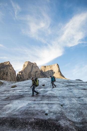 People on rock against sky