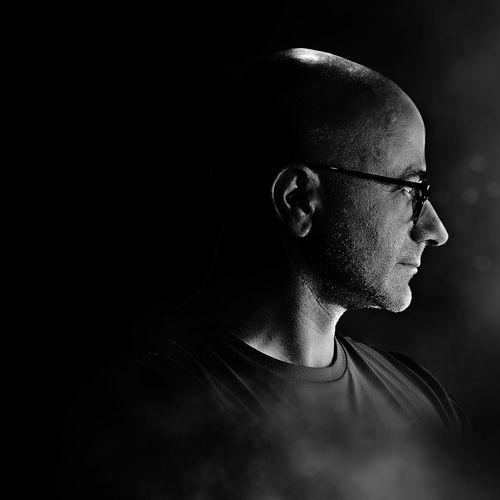 Close-up of mature man wearing eyeglasses against black background