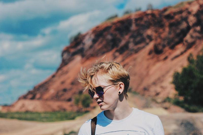 Young woman wearing sunglasses on mountain against sky