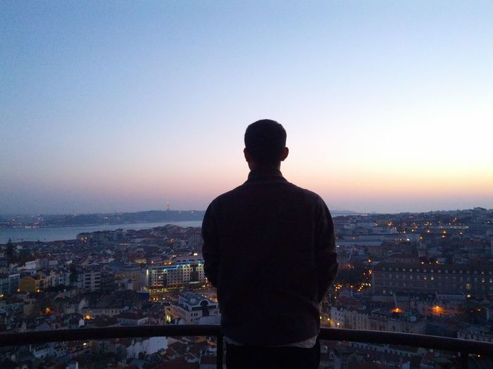 Man overlooking city at dusk