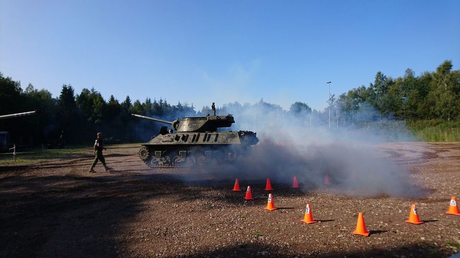 Armored Tank Emitting Smoke On Field Against Clear Blue Sky