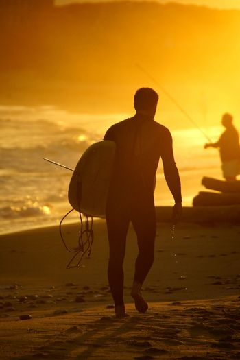 Silhouette Man With Surfboard Walking At Beach During Sunset
