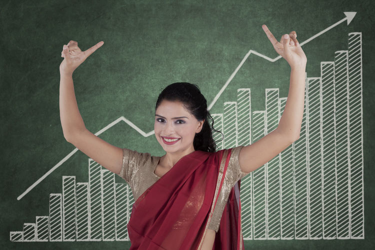 Portrait of smiling young woman in red sari standing against blackboard