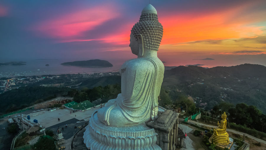 Giant Buddha Statue Against Sky At Sunset