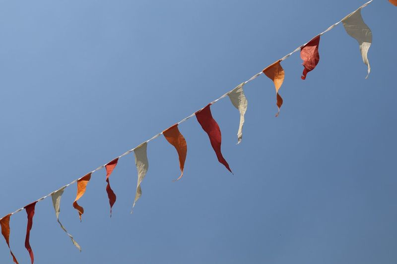 Low angle view of buntings hanging against clear blue sky